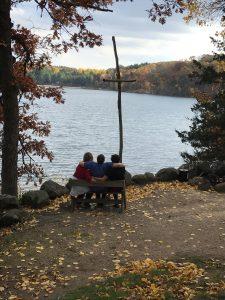 Three people sitting near a lake at Pine Lake United Methodist Camp