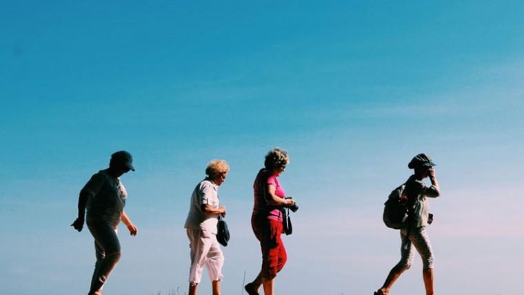 Four women taking a walk against a bright blue sky